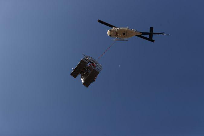 Türkiye Elektrik İletim AŞ (TEİAŞ) canlı bakım ekibi, halatla helikoptere bağlanan sepetin içinde, 170 bin volt enerjinin geçtiği yüksek gerilim hattı