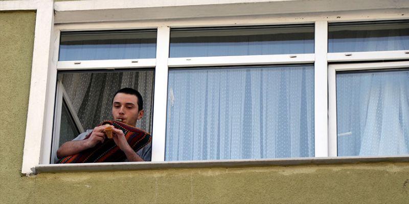 Evinin penceresinden tulumla konser verdi
