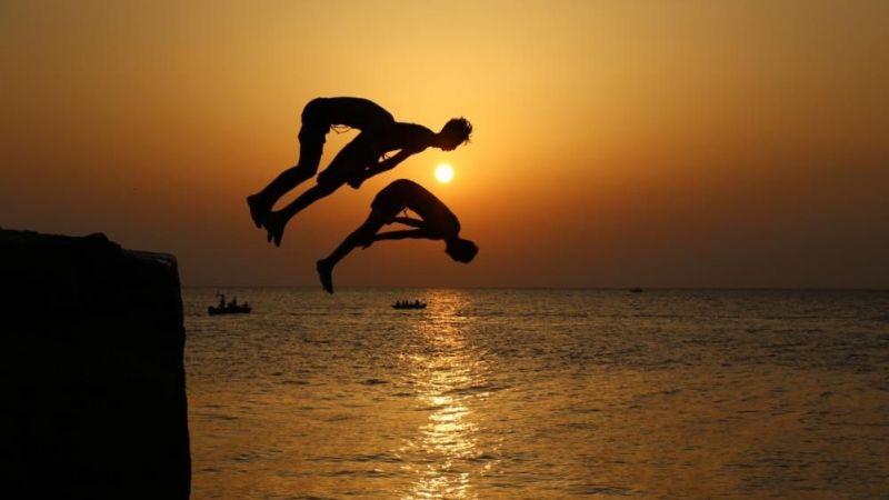 Gün batımında denize atlayan gençler eşsiz görüntüler ortaya çıkardı