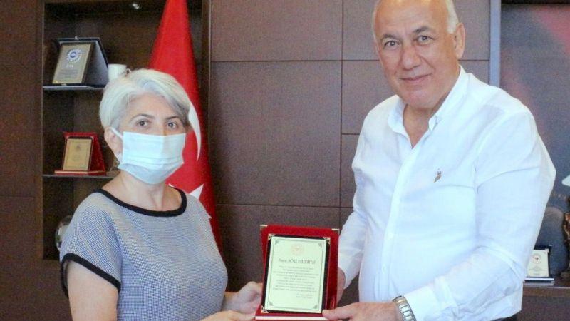 İlçe Sağlık Müdürü pandemi  yardımlarını plaketle ödüllendiriyor