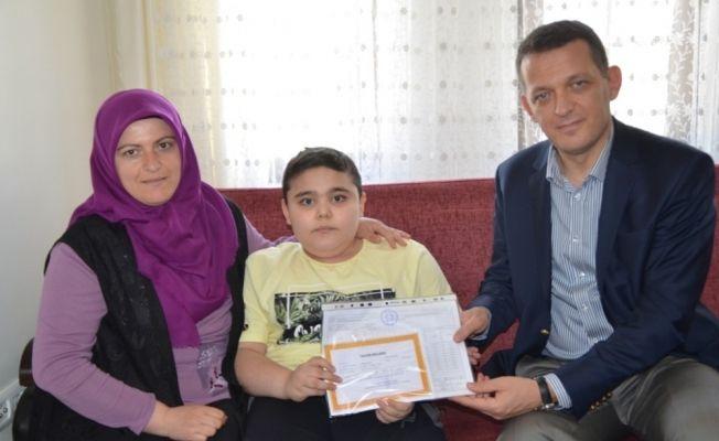 Ürkmezer, DMD hastası Muhammet'e karnesini verdi