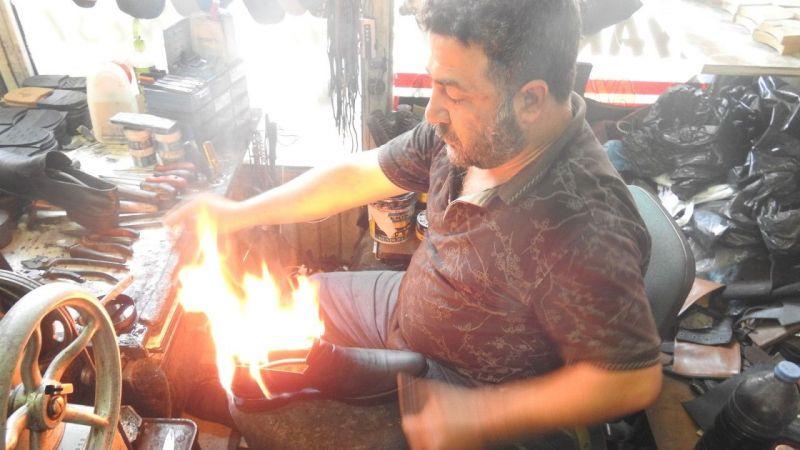 Ayakkabıları 45 derecede ateşle yakarak boyuyor
